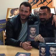 """Ο Γιώργος μαζί με τον φίλο του Μπο κατά τη διάρκεια της παρουσίασης του βιβλίου του """"Ντάνος: Μια αφήγηση στην Αυγή Σαββίδου"""" στα γραφεία της Εκδοτικής Αθηνών που έγινε στις 23 Φεβρουαρίου 2019 Φωτογραφία: ntanos.official.fp Instagram"""